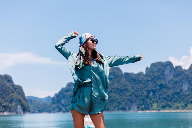 Il giovane turista felice asiatico del blogger della donna in vestito di seta e sciarpa e occhiali da sole in vacanza viaggia intorno alla tailandia sulla barca asiatica, parco nazionale di khao sok. Foto Gratuite