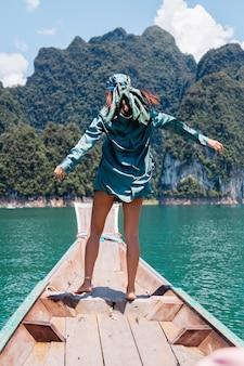 Il giovane turista felice asiatico del blogger della donna in vestito di seta e sciarpa e occhiali da sole in vacanza viaggia intorno alla tailandia sulla barca asiatica, parco nazionale di khao sok.