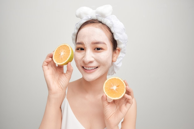 白い顔の粘土マスクを持ち、オレンジ色の部分を保持している若いアジア人。