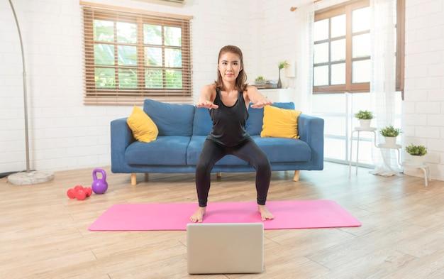 운동복에 젊은 아시아 건강 한 여자는 거실에서 집에서 운동을 스트레칭 피트 니스를 하 고 있습니다. 홈 스포츠 및 레크리에이션 개념.