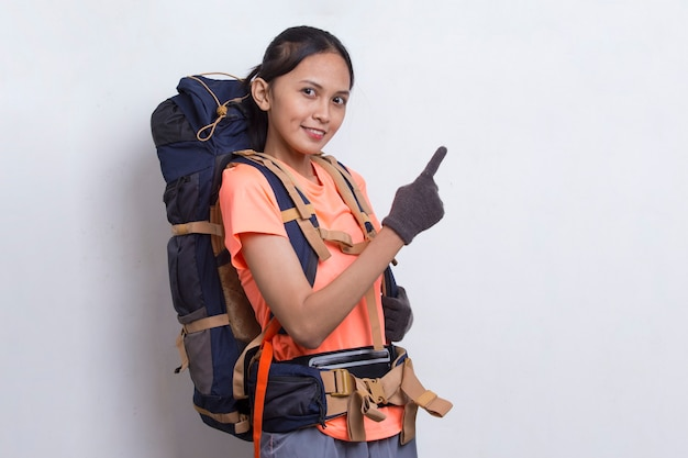 Young asian hiker woman with backpack pointing finger on empty space on white background