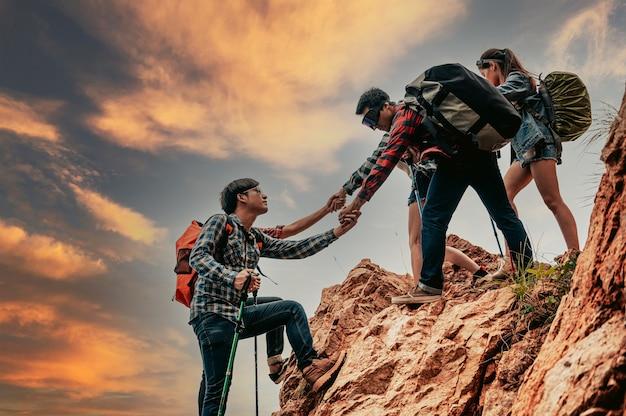 山の頂上に登る若いアジアのハイカーお互いにハイキングを助けている人々