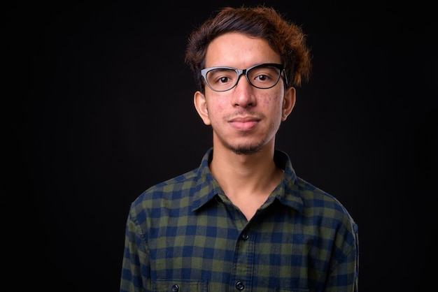 Young asian hipster man with curly hair and acne against black space