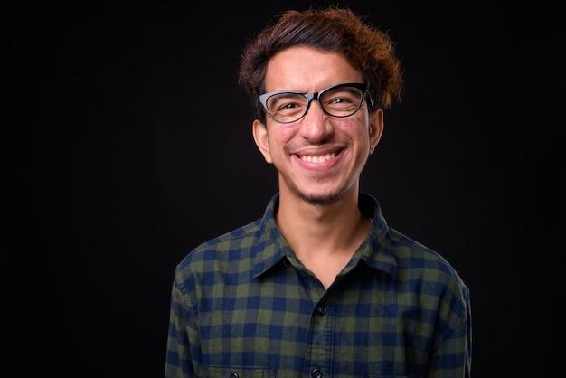 黒いスペースに対して巻き毛とにきびを持つ若いアジアの流行に敏感な男
