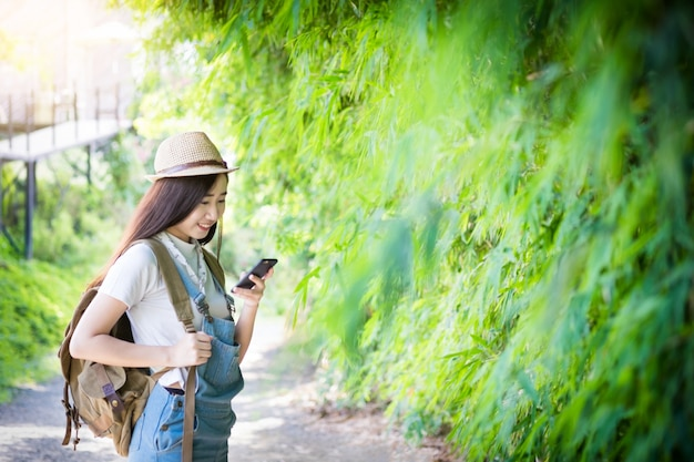 Young asian hipster wear headphone listening to music through smartphone standing outdoors on nature background