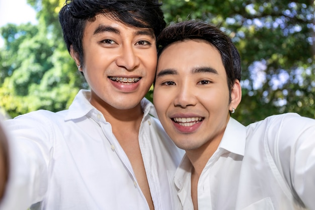 Young asian homosexual couple taking self portrait with smart phone