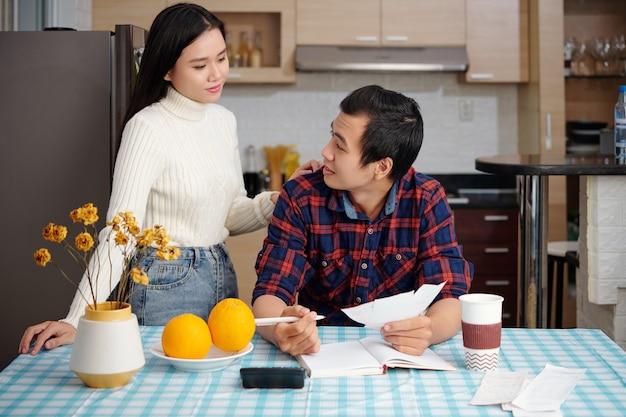 젊은 아시아 후스나드와 아내는 청구서, 계산기, 플래너가 있는 식탁에서 가족 예산을 계획하고 재정을 계산합니다.