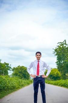 Молодой азиатский / индийский мальчик, стоящий на дороге