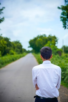Young asian / indian boy standing on the road