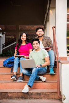 Young asian indian college students reading books, studying on laptop, preparing for exam or working on group project while sitting on grass, staircase or steps of college campus