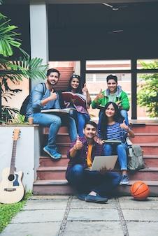 Молодые азиатские индийские студенты колледжа читают книги, учатся на ноутбуке, готовятся к экзамену или работают над групповым проектом, сидя на траве, на лестнице или ступенях кампуса колледжа