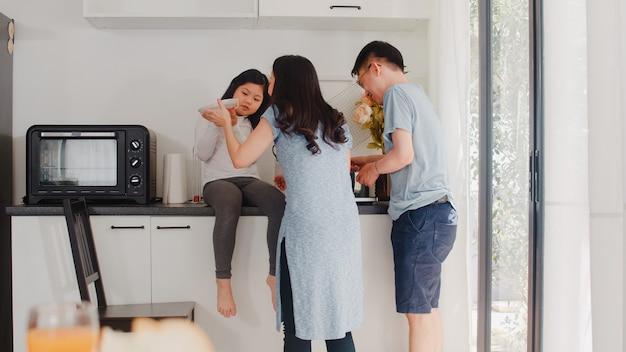 Молодая азиатская японская семья варя дома. образ жизни: счастливая мама, папа и дочь вместе делают макароны и спагетти на завтрак в современной кухне у себя дома по утрам.