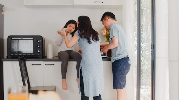 Young asian japanese family cooking at home. lifestyle happy mom, dad, and daughter making pasta and spaghetti together for breakfast meal in modern kitchen at house in the morning .