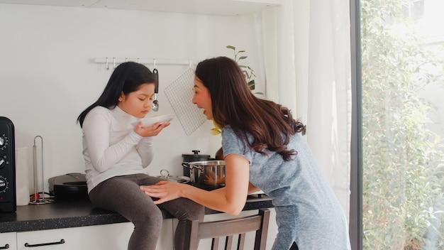 Молодая азиатская японская мама и дочь варя дома. женщины образа жизни счастливые делая макаронные изделия и спагетти совместно для еды завтрака в современной кухне на доме в утре.