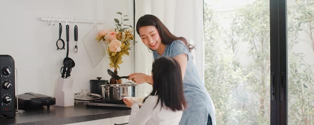 젊은 아시아 일본 엄마와 딸 집에서 요리. 라이프 스타일 여성 아침에 집에서 현대 부엌에서 아침 식사를 위해 파스타와 스파게티를 함께 만드는 행복.