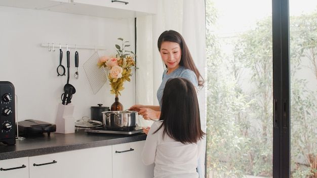 若いアジアの日本人ママと娘が自宅で料理します。朝は家のモダンなキッチンで朝食の食事のためにパスタとスパゲッティを一緒に作る幸せなライフスタイルの女性。