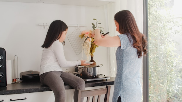 Young asian japanese mom and daughter cooking at home. lifestyle women happy making pasta and spaghetti together for breakfast meal in modern kitchen at house in the morning .