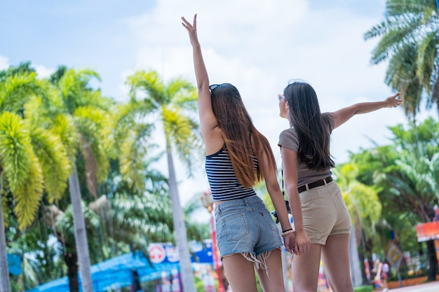 Young asian joyful couple women in summer fashion dress standing in amusement park. concept happy and lovely life of teenager.