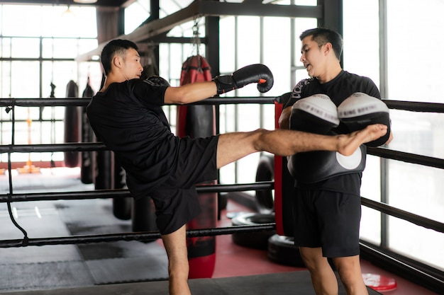 Young asian kick boxer kicking professional trainer in boxing stadium