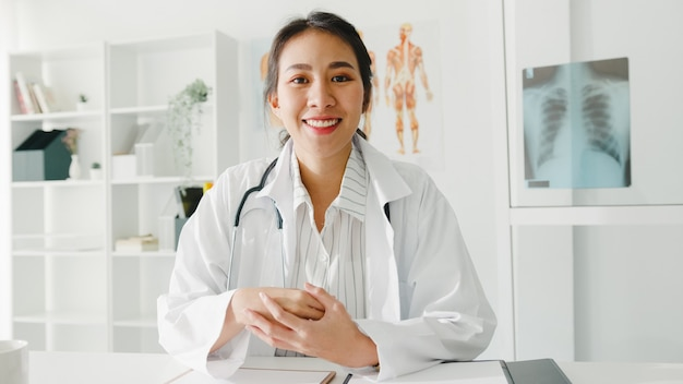 컴퓨터 노트북을 사용하는 청진기와 흰색 의료 제복을 입은 젊은 아시아 여자 의사