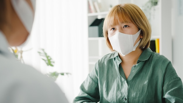 Young asian lady doctor wear protective mask using clipboard discussing results or symptoms with girl patient in hospital office.