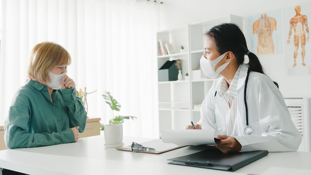 Young asian lady doctor wearing protective mask using clipboard discussing results or symptoms with girl patient in hospital office.