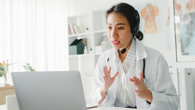 Young asian lady doctor in white medical uniform with stethoscope using computer laptop