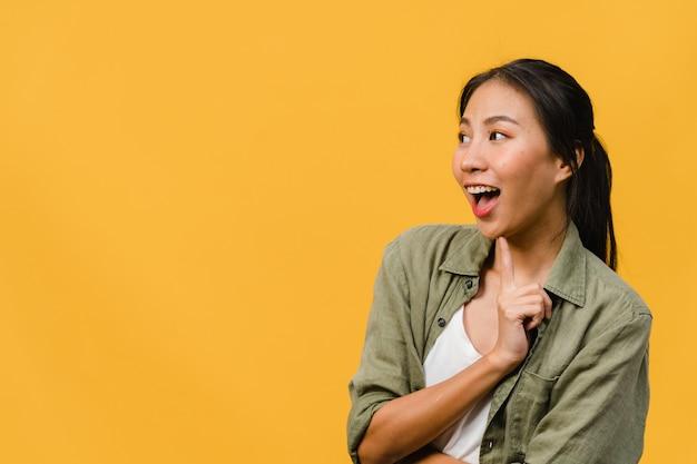La giovane donna asiatica si sente felice con l'espressione positiva, gioiosa sorpresa funky, vestita con un panno casual isolato sul muro giallo. la donna felice adorabile felice si rallegra del successo. espressione facciale.