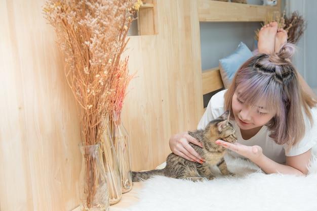 침대에 고양이와 젊은 아시아 아가씨 놀이