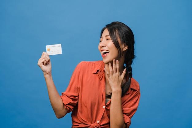 若いアジアの女性は、前向きな表情でクレジットカードを表示し、広く笑顔で、幸せを感じるカジュアルな服を着て、青い壁に孤立して立っています。表情のコンセプト。