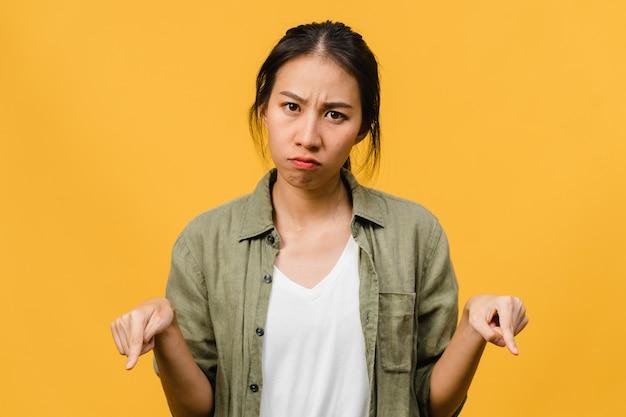 Молодая азиатская дама показывает что-то удивительное на пустом месте с негативным выражением лица, взволнованный крик, плач, эмоциональный гнев, изолированный над желтой стеной. концепция выражения лица.