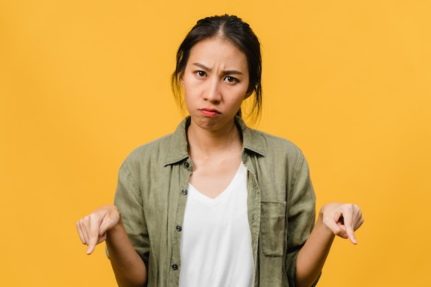 Young asian lady shows something amazing at blank space with negative expression, excited screaming, crying emotional angry isolated over yellow wall. facial expression concept.