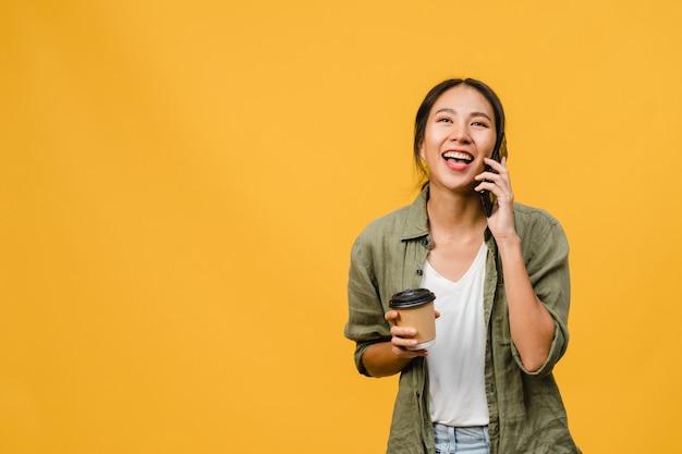 若いアジア人女性は電話で話し、前向きな表情でコーヒーカップを持ち、広く笑顔で、幸せを感じるカジュアルな服を着て、黄色い壁に孤立して立っています。表情のコンセプト。