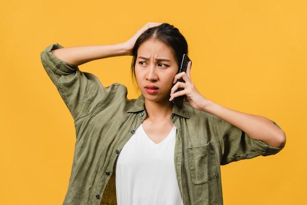 La giovane signora asiatica parla al telefono con espressione negativa, urla eccitata, piange emotivamente arrabbiata in un panno casual e sta isolata sul muro giallo con spazio vuoto per la copia. concetto di espressione facciale.