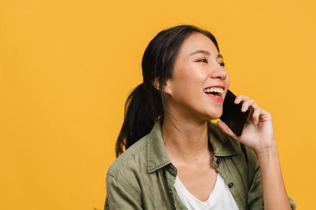 La giovane donna asiatica parla al telefono con espressione positiva, sorride ampiamente, vestita con abiti casual sentendosi felice e sta isolata sul muro giallo. la donna felice adorabile felice si rallegra del successo.