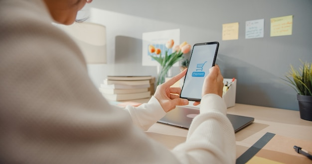 Young asian lady use cellphone order online shopping product and paying bills with banking app with transaction successful. stay at house, quarantine activity, fun activity for coronavirus prevention.