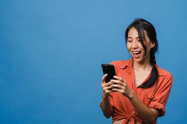 ポジティブな表情で電話を使用している若いアジアの女性は、広く笑顔で、幸せを感じてカジュアルな服を着て、青い壁に孤立して立っています。幸せな愛らしい嬉しい女性は成功を喜んでいます。