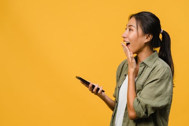 ポジティブな表情で電話を使用している若いアジアの女性は、広く笑顔で、幸せを感じてカジュアルな服を着て、黄色い壁に孤立して立っています。幸せな愛らしい嬉しい女性は成功を喜んでいます。
