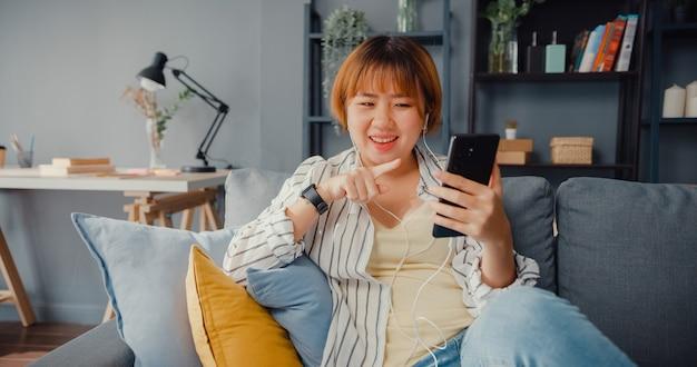 집에서 거실에 소파에 가족과 함께 스마트 폰 화상 통화 이야기를 사용하는 젊은 아시아 아가씨