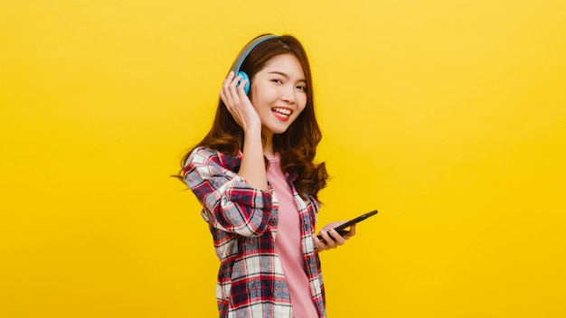 Young asian lady wearing wireless headphones listening to music from smartphone with cheerful expression in casual clothing and looking at camera over yellow wall. facial expression concept.
