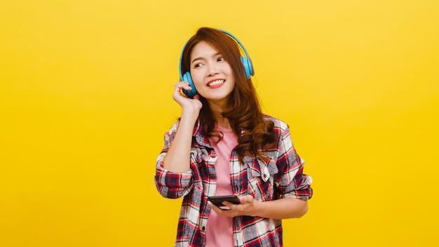 カジュアルな服装で陽気な表情でスマートフォンから音楽を聴くと黄色の壁越しにカメラを見てワイヤレスヘッドフォンを着ている若いアジア女性。顔の表情のコンセプトです。