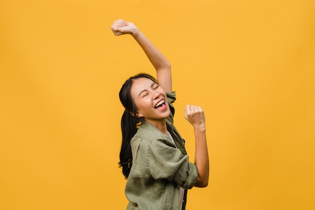 Young asian lady with positive expression, joyful and exciting, dressed in casual cloth over yellow wall with empty space. happy adorable glad woman rejoices success. facial expression concept.