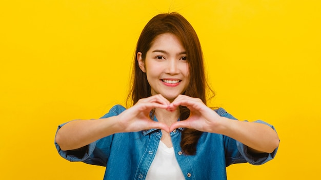 Young asian lady with positive expression, shows hands gesture in heart shape, dressed in casual clothing and looking at the camera over yellow wall. happy adorable glad woman rejoices success.