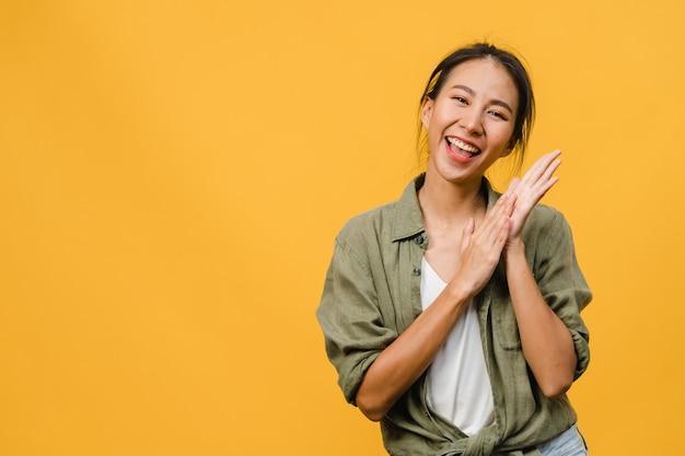 Giovane signora asiatica con un'espressione positiva, sorride ampiamente, vestita con abiti casual sul muro giallo. la donna felice adorabile felice si rallegra del successo. concetto di espressione facciale.