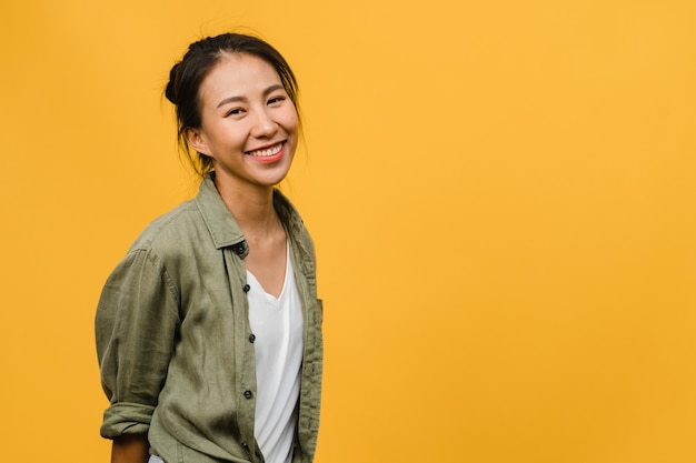 Young asian lady with positive expression, smile broadly, dressed in casual clothing  over yellow wall. happy adorable glad woman rejoices success. facial expression concept.