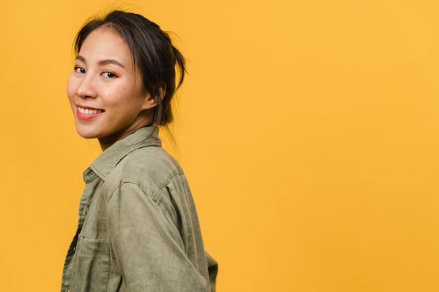 黄色い壁にカジュアルな服を着て、前向きな表情をしたアジアの若い女性。幸せな愛らしい嬉しい女性は成功を喜んでいます。表情のコンセプト。