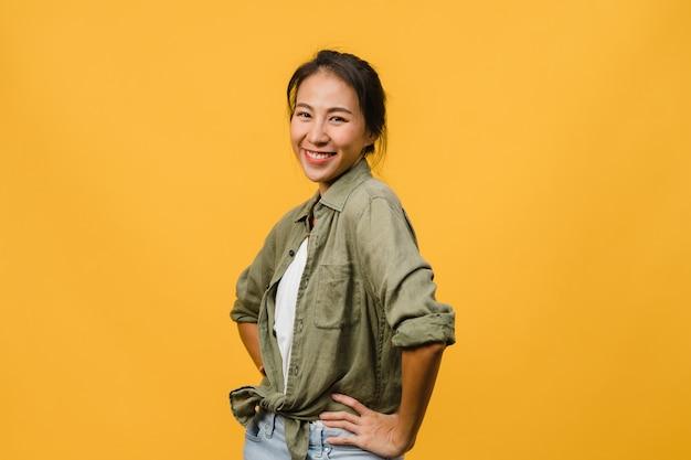 Молодая азиатская дама с позитивным выражением лица, широко улыбается, одетая в повседневную одежду над желтой стеной. счастливая очаровательная рада женщина радуется успеху. концепция выражения лица.