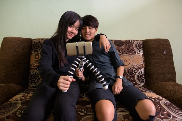 Young asian lesbian couple sitting on the sofa together
