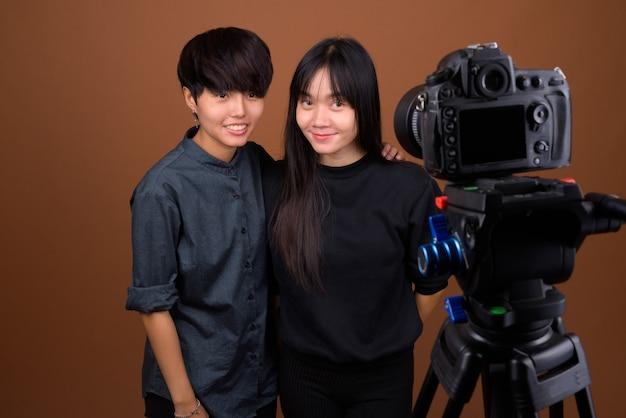 若いアジアのレズビアンのカップルが一緒に、茶色に恋して