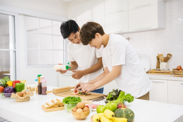 Young asian lgbt couple together cook sandwich by put ham, tomato, vegetable on bread at kitchen. healthy eating lifestyle for homosexual same sex family at home.